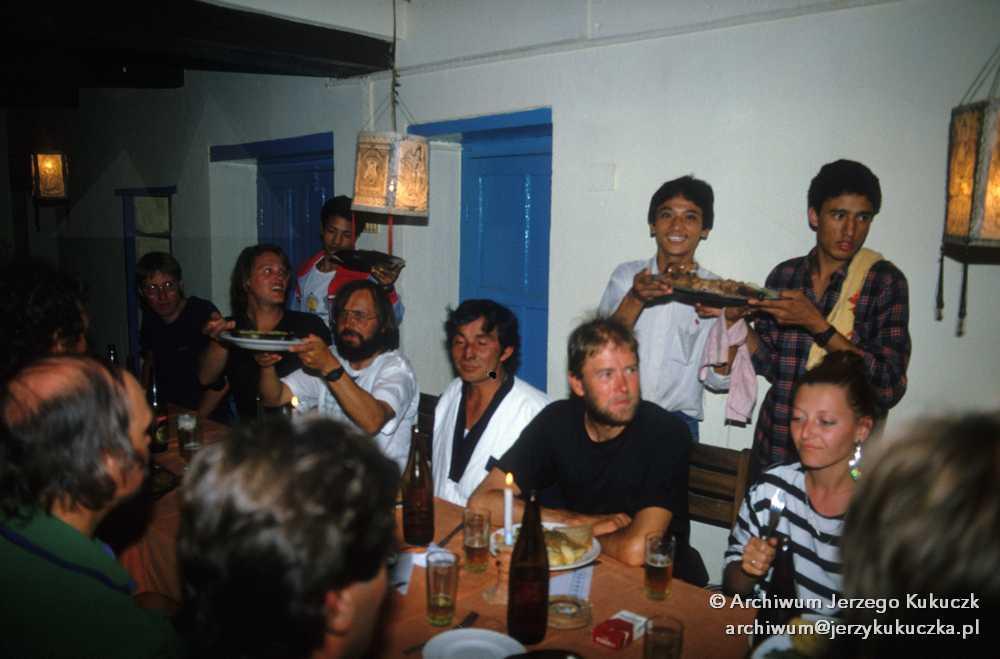 Impreza, czwarty od lewej Ryszard Warecki podnosi talerz z jedzeniem.
