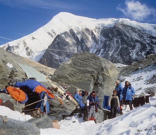 Pośrodku kierownik Adam Bilczewski wraz z pozostałymi uczestnikami wyprawy w bazie pod Dhaulagiri. Na drugim planie charakterystyczny głaz