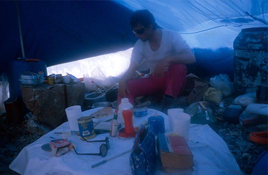 Wojtek Kurtyka, surrounded by the kitchen assortment in the base camp mesa