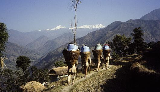 Droga do bazy pod Kangchenjungą. Na pierwszym planie widoczni tragarze niosący wyposażenie wyprawy